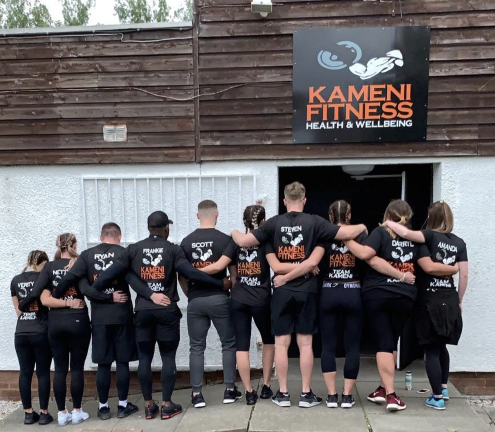 Group standing with their back to the camera wearing branded Kamei Fitness tshirts outside Kameni Fitness gym